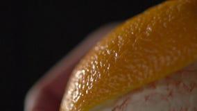 La mano quita la cáscara de la naranja almacen de video
