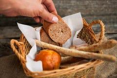 La mano raggiunge per il pane in un canestro immagine stock libera da diritti