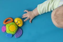 La mano reci?n nacida del ni?o estira a la derecha al juguete de una tortuga multicolora con una sonrisa en un fondo azul Cierre imagen de archivo