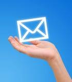 La mano recibe el icono de la carta del email foto de archivo