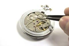 La mano ripara un vecchio orologio meccanico Isolato Immagine Stock