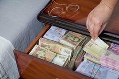 La mano saca el billete de banco de la mesita de noche Foto de archivo libre de regalías