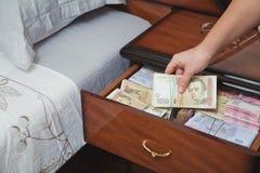 La mano saca el taco del dinero de la mesita de noche Imagenes de archivo