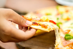 La mano sacaba una pizza Fotos de archivo libres de regalías