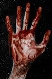 La mano sanguinosa sul vetro bagnato, la finestra sanguinosa, un'impronta delle mani sanguinose, zombie, demone, uccisore, orrore Fotografia Stock