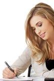 La mano scrive con una penna in un taccuino Immagine Stock