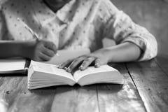 La mano scrive con una penna in un taccuino Fotografie Stock