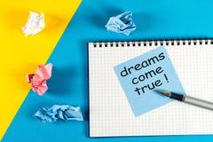 La mano scrive i sogni avverati - sul messaggio al blocco note, fondo blu Fotografie Stock Libere da Diritti