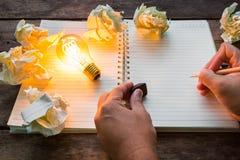 La mano scrive sopra il taccuino e la lampadina Fotografia Stock Libera da Diritti