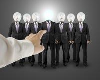 La mano señala a un hombre de negocios con la cabeza de la bombilla Imagen de archivo libre de regalías