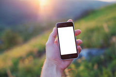 La mano sinistra degli uomini sta tenendo un telefono con lo schermo bianco Immagini Stock