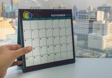 La mano sinistra della donna di affari tiene il calendario del novembre 2018 per il ricordo di appuntamento Fotografie Stock