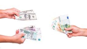 La mano sostiene billetes de banco del euro, del dólar y de la rublo Aislado en el fondo blanco Fotos de archivo
