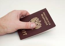 La mano sostiene el pasaporte Imagen de archivo libre de regalías