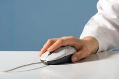 La mano sostiene el ratón del ordenador Foto de archivo