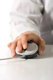 La mano sostiene el ratón del ordenador imagenes de archivo