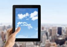 La mano sostiene la PC de la tablilla con el cielo en la pantalla Fotografía de archivo