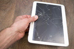 La mano sostiene la tableta con la pantalla táctil quebrada Imagenes de archivo
