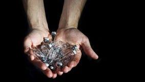 La mano sostiene las ampollas de cristal de la medicina, insulina vacía en los vagos negros Imagen de archivo libre de regalías