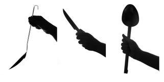 La mano sostiene las herramientas de la cocina. conjunto Imágenes de archivo libres de regalías