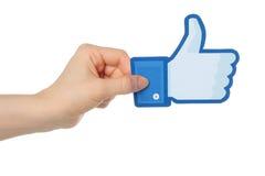 La mano sostiene los pulgares del facebook encima de la muestra fotografía de archivo libre de regalías