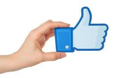 La mano sostiene los pulgares del facebook encima de la muestra impresa en el documento sobre el fondo blanco Fotos de archivo