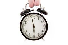 La mano sostiene un despertador Foto de archivo libre de regalías