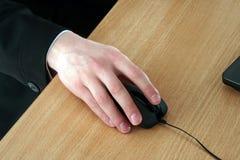 La mano sostiene un ratón del ordenador Foto de archivo libre de regalías