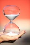 La mano sostiene un reloj de arena moderno Símbolo del tiempo countdown Foto de archivo libre de regalías