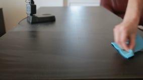 La mano sostiene un trapo azul y limpia su saca el polvo apagado de la tabla almacen de metraje de vídeo