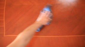 La mano sostiene un trapo azul y limpia su saca el polvo apagado de la tabla metrajes