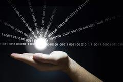 La mano sostiene una bola que brilla intensamente que emite datos Fotos de archivo