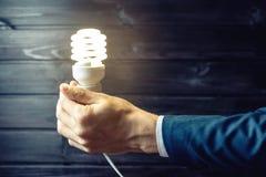 La mano sostiene una bombilla que brilla intensamente Idea creativa en negocio Foto de archivo libre de regalías