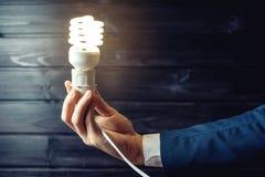 La mano sostiene una bombilla que brilla intensamente Idea creativa en negocio Fotos de archivo