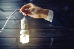 La mano sostiene una bombilla que brilla intensamente Idea creativa en negocio Fotos de archivo libres de regalías