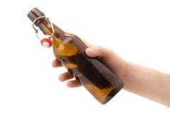 La mano sostiene una botella de cerveza. Fotos de archivo libres de regalías