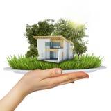 La mano sostiene una placa. En la placa es una pequeña casa ilustración del vector