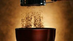 La mano spruzza il cacao in una ciotola su fondo dorato - movimento lento stock footage