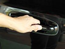 La mano sta andando tirare una maniglia di portello dell'automobile Fotografia Stock