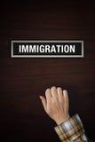 La mano sta battendo sulla porta dell'ufficio di immigrazione Fotografie Stock Libere da Diritti