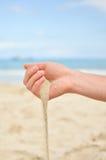 La mano sta giocando con la sabbia Fotografia Stock