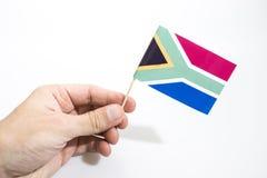 La mano sta giudicando la bandiera della Sudafrica isolata in un fondo bianco fotografia stock