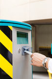 La mano sta inserendo il biglietto di parcheggio nella barriera del g Fotografia Stock Libera da Diritti