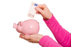 La mano sta mettendo un euro non in un porcellino salvadanaio Fotografie Stock Libere da Diritti