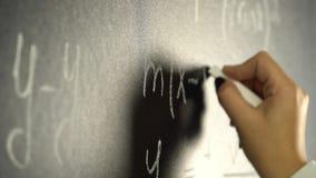 La mano sta scrivendo con un gesso un matematico di una formula su una lavagna archivi video