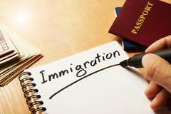 La mano sta scrivendo l'immigrazione immagini stock