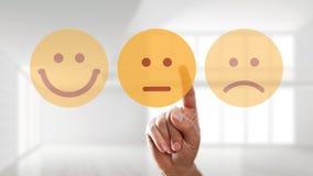 La mano sta selezionando uno smiley neutrale dell'umore immagini stock libere da diritti