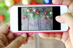 La mano sta tenendo il telefono per prendere le foto delle decorazioni di Natale Fotografia Stock Libera da Diritti