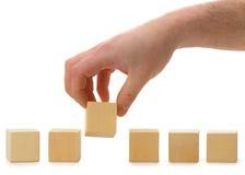 La mano stabilisce un cubo di legno nella riga immagine stock libera da diritti