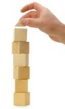 La mano stabilisce un tetto del giocattolo sui cubi di legno Immagine Stock Libera da Diritti